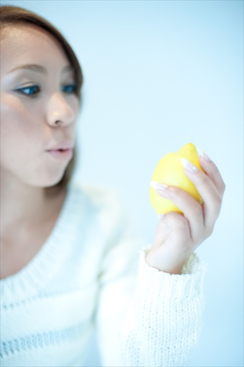 レモンを手に持つ女性の画像