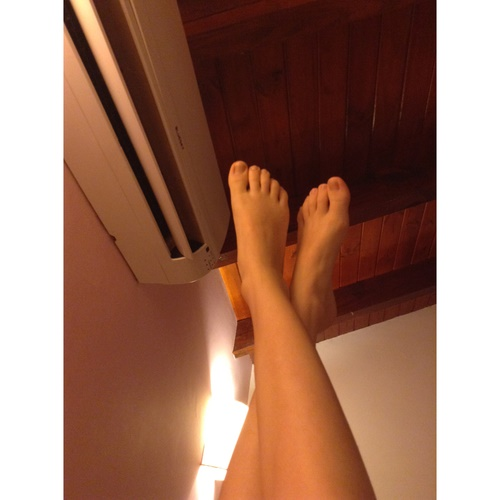 クーラーに脚をあてる女性の画像