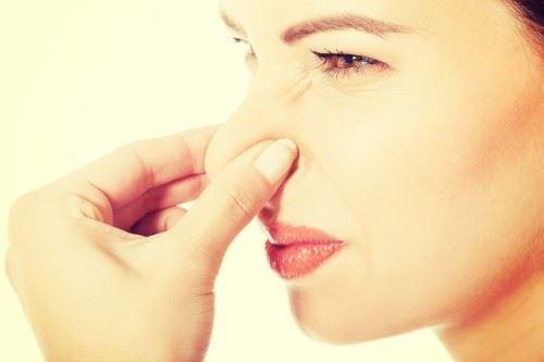鼻をつまんでクサイ反応をする女性