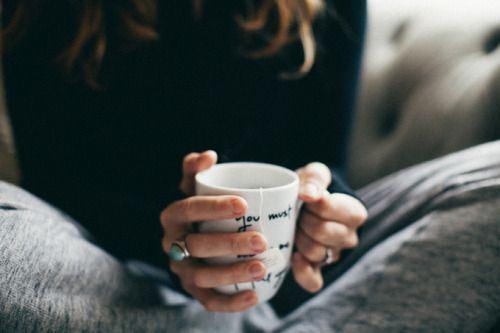 温かい飲み物で手を温める女性
