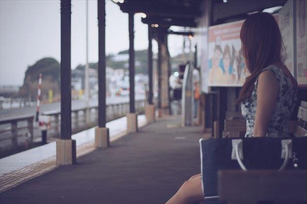 江ノ電のホームで海を眺める女性