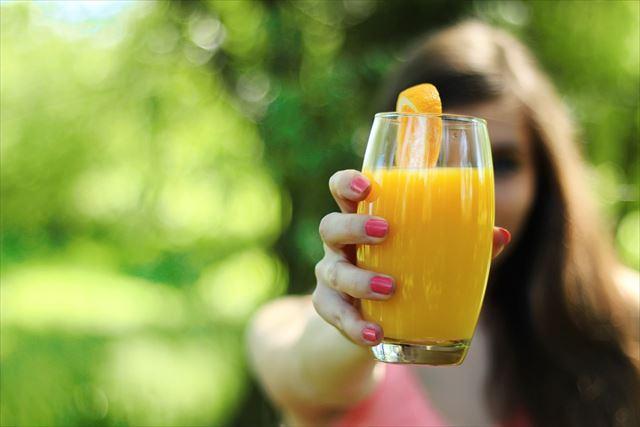 オレンジベースの野菜ジュースを持つ女性