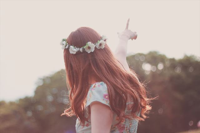 キレイな髪を手に入れて空を指差す女性