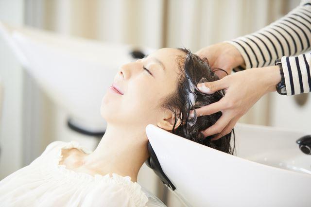 美容室のサロンシャンプーで髪を洗われる女性の画像