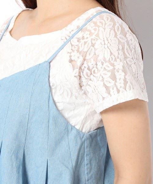 白レーストップスにブルーのキャミソールを重ね着した女性のバストトップ画像