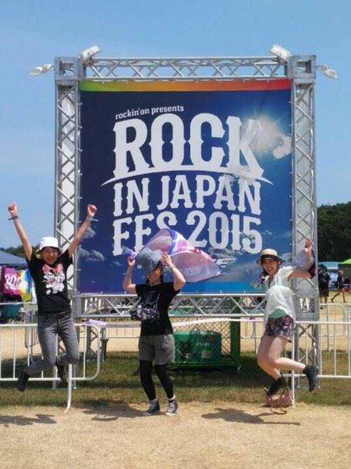 夏フェスの会場前でジャンプする女性3人の画像