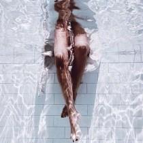 プールの中に脚を入れる女性の画像