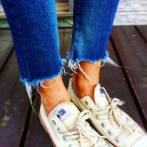 ブルーの切りっぱなしデニムと白いコンバースオールスターをはいた足元の女性の画像