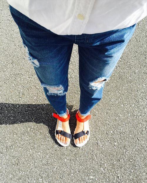 ブルーの切りっぱなしデニムとTeva系スポーツサンダルをはいた女性の足元の画像