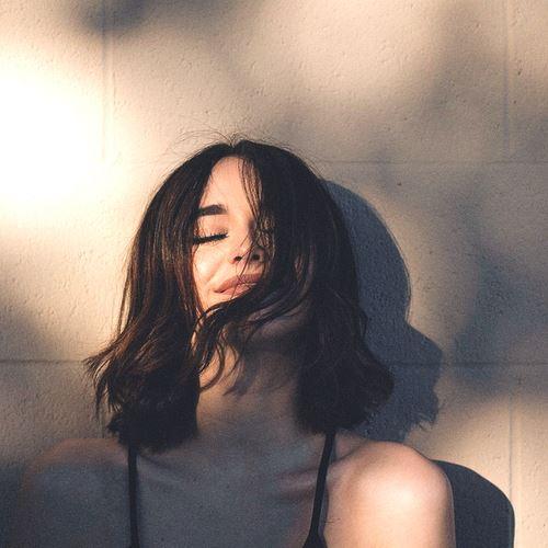 香りの良い髪のにおいで笑顔になっている女性の画像