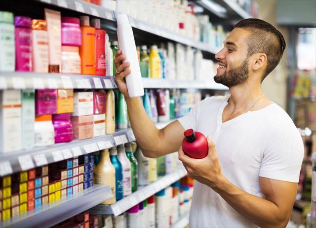 たくさんの市販メンズシャンプーから商品を選ぶ男性の画像