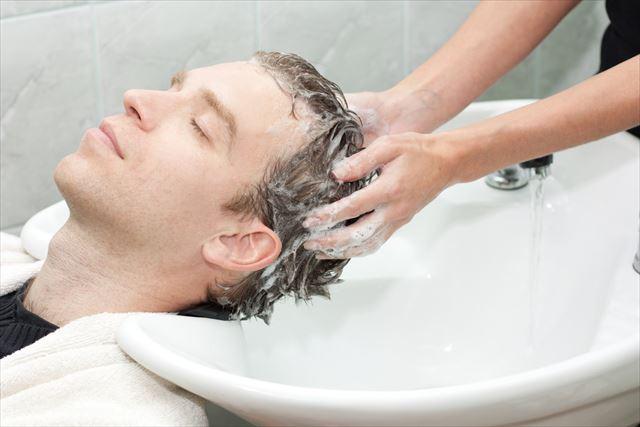 美容室でシャンプーをしてもらう男性の画像