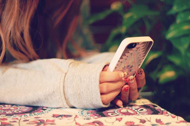 最新の人気アプリをiPhoneで楽しむ女性の画像1