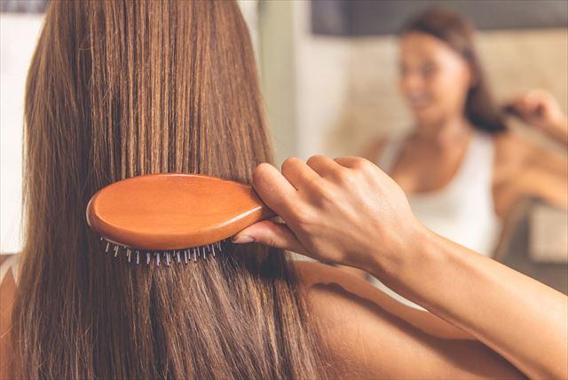 シャンプー前に髪をとかす女性の画像