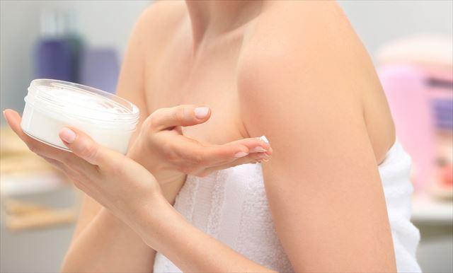 ボディクリームを手に取る女性の画像