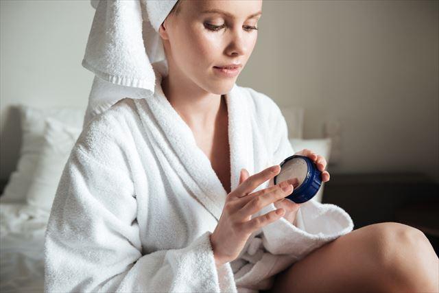 お風呂上りにボディクリームを手に取る女性の画像