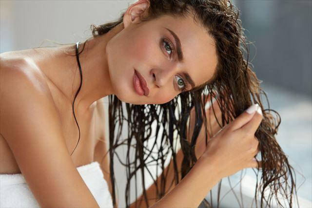 トリートメント後の濡れた髪にヘアオイルをつける女性の画像