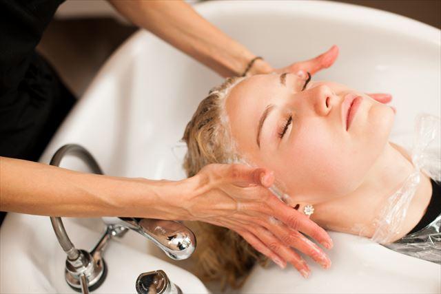 美容室で新発売のシャンプーで髪を洗われる女性の画像