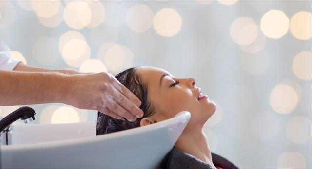 自分にあった最新シャンプーで髪を洗う女性の画像