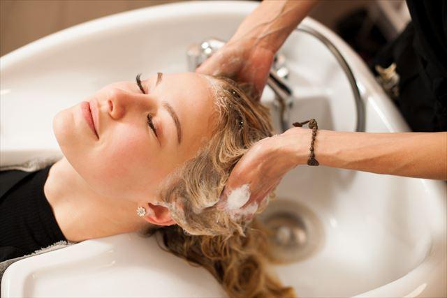 アミノ酸シャンプーで美容師に洗髪される女性の画像
