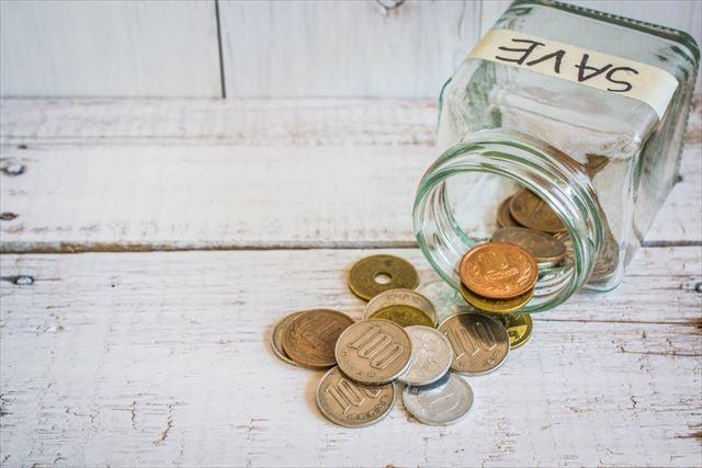貯金箱と小銭の画像