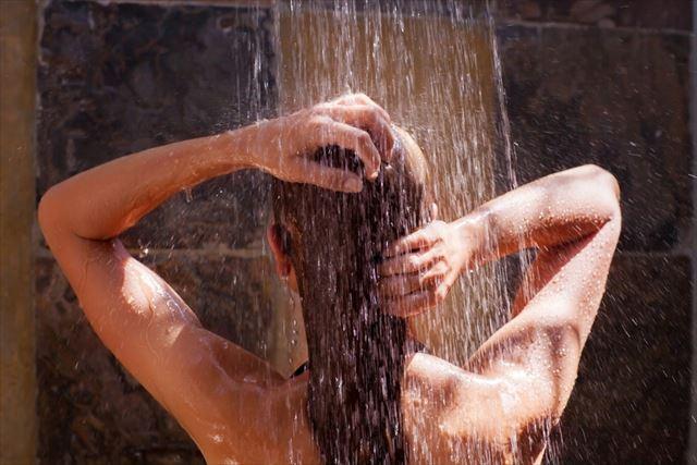シャンプー後に髪を洗い流す女性の画像