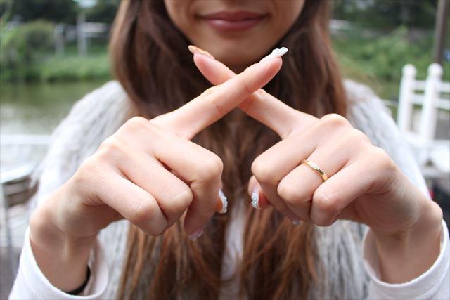 指でバッテンマークを作る女性の画像