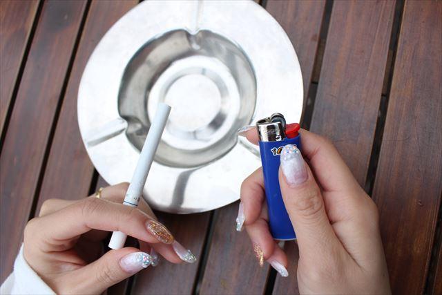 灰皿の上でライターと紙タバコを持った画像