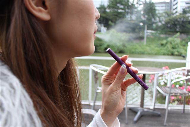 カフェのテラス席でビタフルを吸う女性の画像