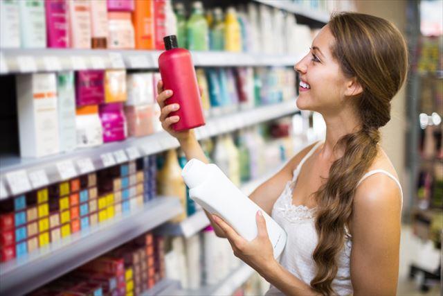 シャンプーボトル裏に書かれた洗浄成分を確認する女性の画像
