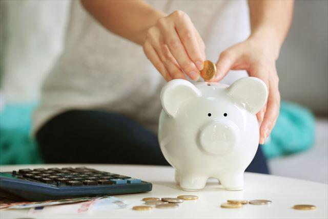 貯金箱にお金を溜める女性の画像