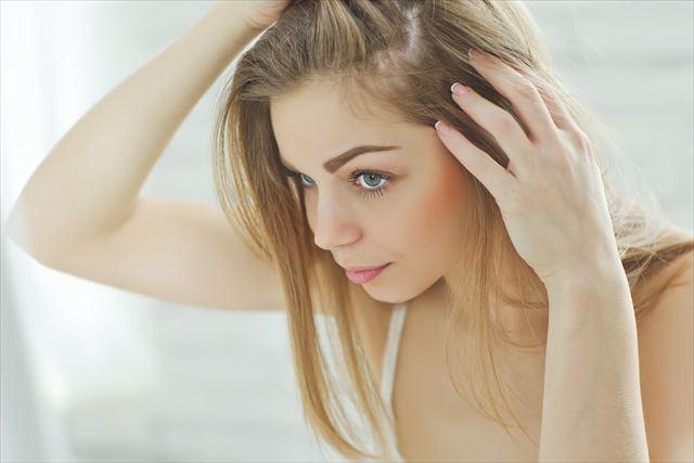 髪の生え際を気にする女性の画像
