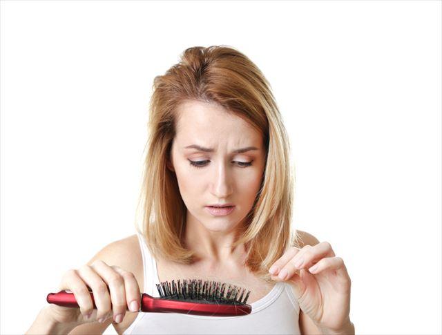 抜け毛を気にする女性の画像