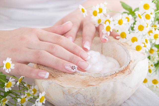 ハンドクリームを塗る女性の手指の画像