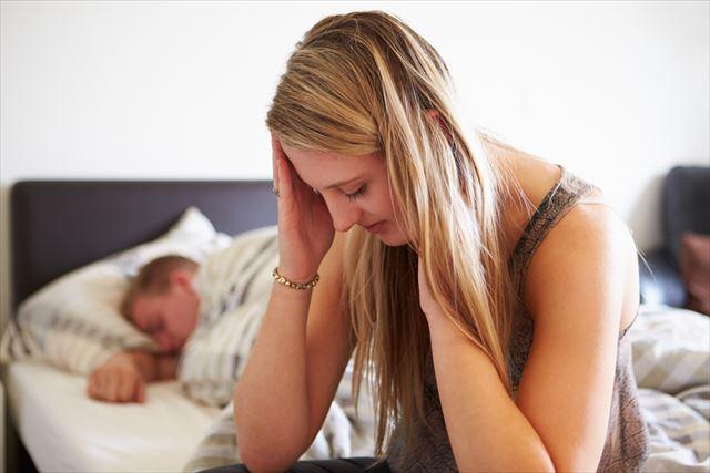 ベッドサイドでバストトップの黒ずみに悲しむ女性の画像