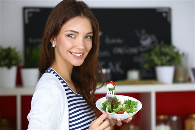 栄養たっぷりのサラダを食べる女性の画像