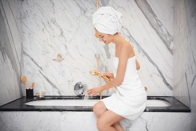 バスルームでシャワーの水圧をチェックする女性の画像
