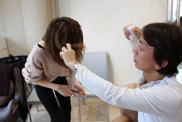 ZACCトリートメントミストをスタッフの髪で試す開発者の高橋和義さんの画像1