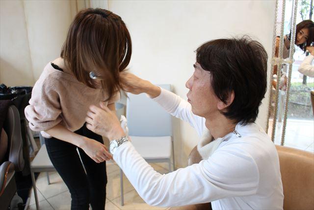 ZACCトリートメントミストをスタッフの髪につけてなじませる開発者の高橋和義さんの画像