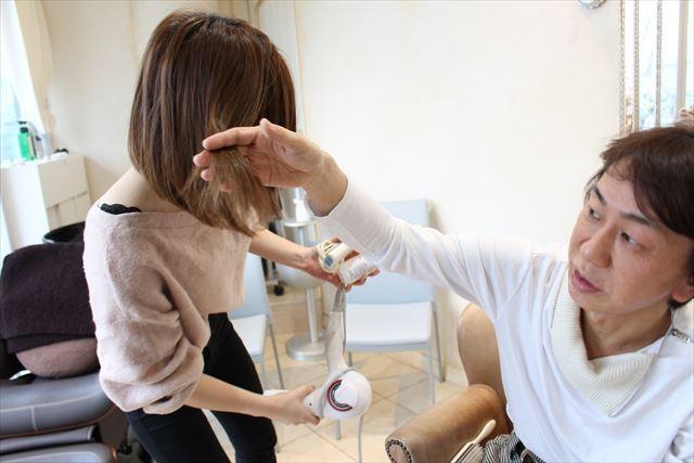 ZACCトリートメントミストをつけたスタッフの髪を確認する開発者の高橋和義さんの画像