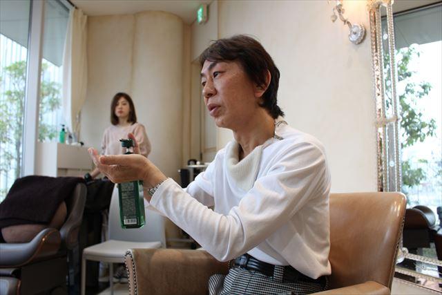 ZACCスカルプシャンプーのボトルを持ちながらテクスチャーについて説明する開発者の高橋和義さんの画像