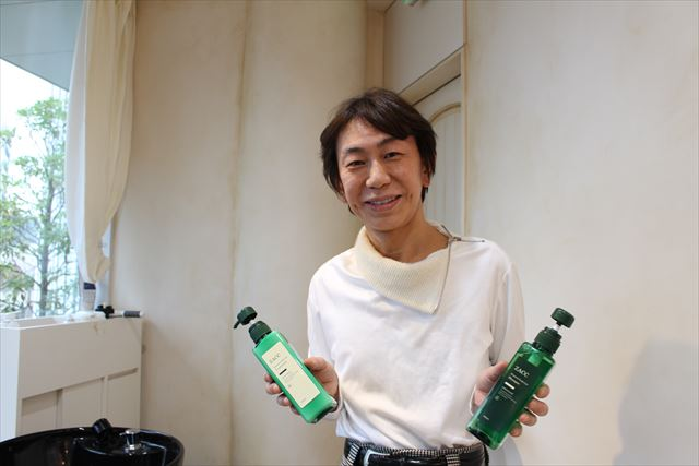 ZACCスカルプのシャンプーとコンディショナーを持つ代表の高橋和義さんの画像