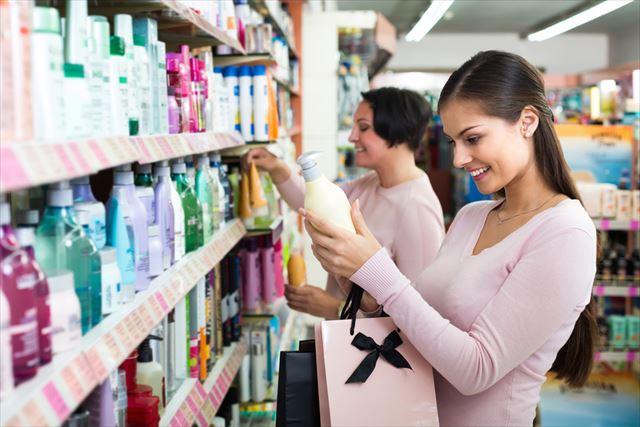 ドラッグストアで最新のトレンドシャンプーを手に取る女性の画像