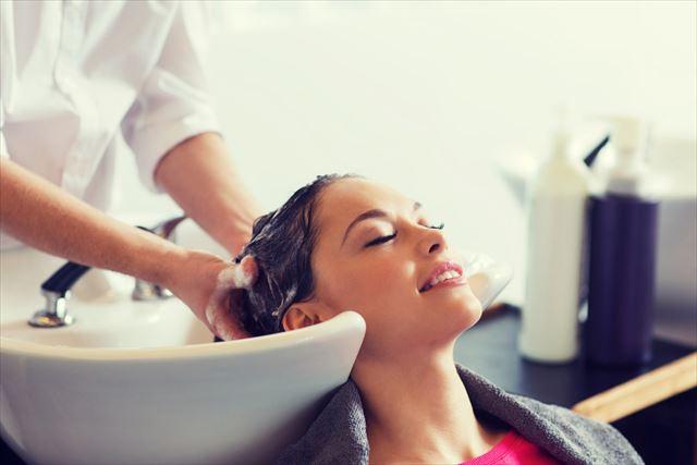 美容室のスカルプシャンプーで髪を洗う女性の画像