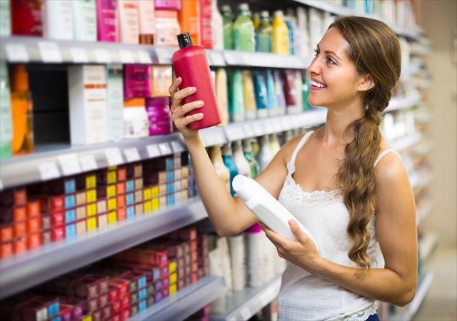 薬局で炭酸シャンプーを物色する女性の画像