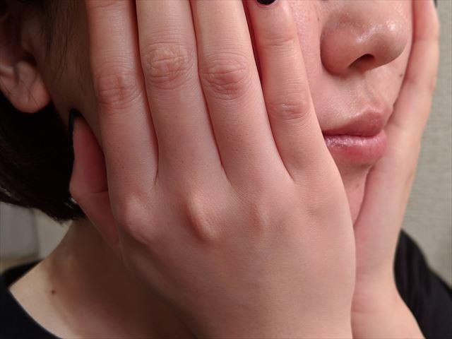 顔全体を手のひらで包み込む画像