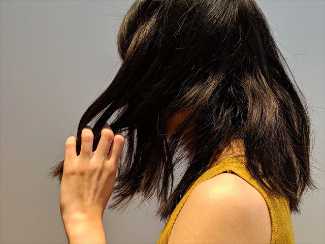 ボサボサの髪をさわる女性の画像