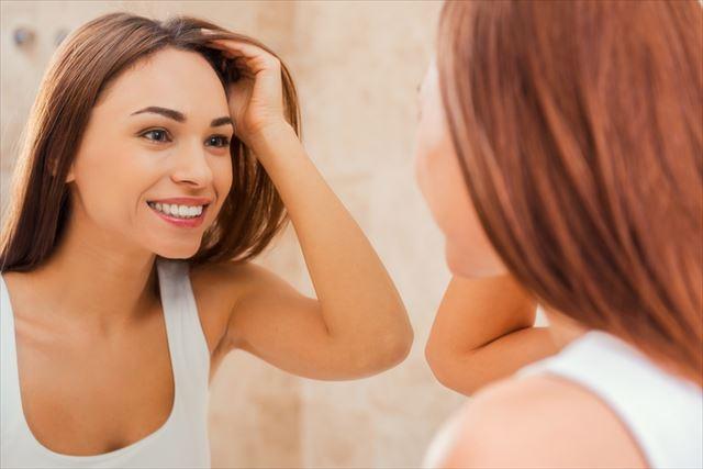 メイク後の顔を見る女性の画像